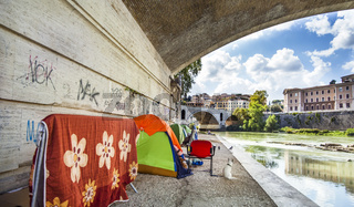 Tents of homeless people under a bridge on the Tiber in Rome Italy