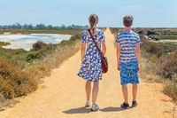 Mother and son walking on sandy path in coastal area