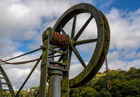 Detail of old steel cargo winch on harbour by tidal River Tamar in Devon