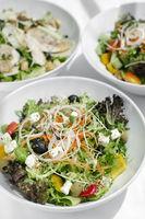 mixed fresh organic salads on white restaurant table