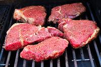 Raw seasoned steaks on a BBQ grill