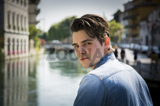 Young man wearing denim shirt on city bridge in Treviso