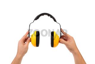 Hands holds working protective headphones.