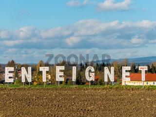 Schriftzug Enteignet auf einem Feld
