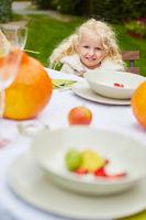 Mädchen sitzt am gedeckten Tisch im Garten