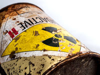Radiation warning sign on the rusty and decay radioactive material container