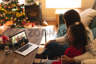 Woman and daughter sitting on the couch having a videocall with man and son in santa hats waving on