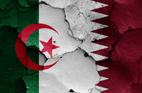 flags of Algeria and Qatar painted on cracked wall