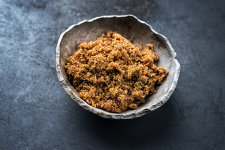 Traditional brown muscovado sugar offered as closeup in a rustic earthenware dish with copy space