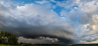 Dramatic cloudy sky with circular thunderstorm cloud over countryside  hills