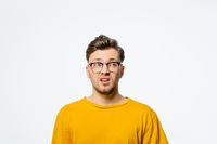 Handsome young man in eye glasses shocked with surprise expression, fear and excited on his face.Young casual man portrait isolated on yellow background