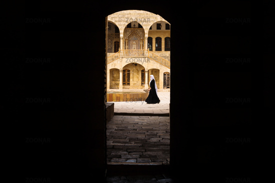 View trough entrance tunnel with lady passing by at Emir Bachir Chahabi Palace Beit ed-Dine, Lebanon