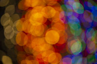 Multi-colored large bokeh spots of blue, yellow and orange. Bokeh from a Christmas garland.