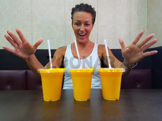 Happy Woman Looking At Mango Lassi Drink Inside Indian Restaurant With Arms Raised