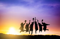 The Silhouette of  graduation group celebrating and jumping on mountain