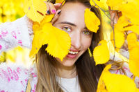 Portrait of a beautiful girl hiding her face behind autumn leaves closeup