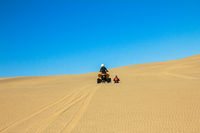 Quad driving people - two happy bikers in sand desert dunes, Africa, Namibia, Namib, Walvis Bay, Swakopmund.