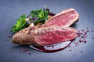 Fried dry aged venison tenderloin fillet medallion steak natural with kalette and raspberry sauce as closeup on a modern design plate
