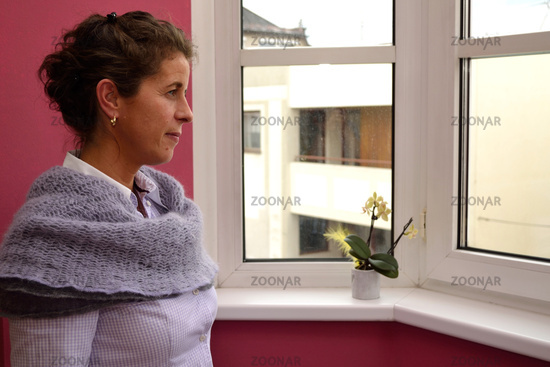 Woman looking pensively out the window