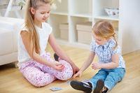 Geschwister spielen mit Karten zu Hause