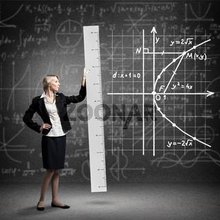 Young mathematics teacher holding big ruler