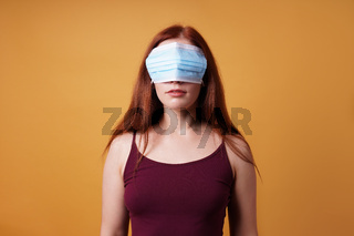 young woman wearing medical face mask over her eyes - corona denier