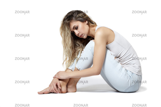 Young pretty in jeans and shirt woman sitting on gray background