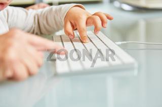 Hand von Vater hilft Kleinkind am Computer