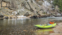 inflatable whitewater kayak on a rocky shore of a mountain river