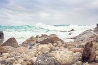 Large waves surge onto the rocky shore of Sydney headland cliffs