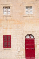 Red door and windows traditional stone wall house mdina Malta
