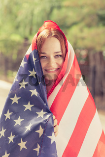 Smiling girl covered with US flag
