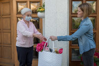 Senior woman with face mask gets shopping bag from young neighbor woman at the house door