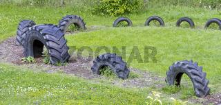 Wiese mit halb eingegrabenen Traktorreifen