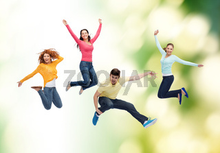 group of smiling teenagers jumping in air