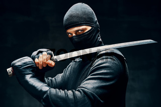 Fighting ninja posing with a sword over black background