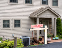 Mockup of foreclosure sign in front of modern townhome due to recession and pandemic