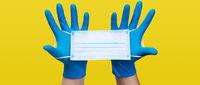 Hands in medical gloves hold medical protective mask.