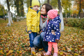 The family walks in the autumn park on a cloudy day