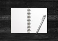 Blank open spiral notebook and pen isolated on black wood background