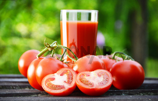 Tomatoes and juice in the garden. Organic food.