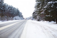 Snowy street surrounded by pine trees, winter road in the forest. Freezing day.