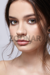 Beauty portrait of young woman on gray background.
