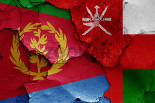flags of Eritrea and Oman painted on cracked wall