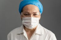 Female doctor face, close up shot. Mature woman in protective mask and goggles looks at camera. Isolated on gray