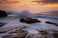 Coastal sunrise waves crashing onto rocks