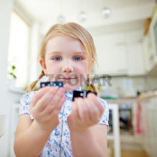 Kind hält zwei Dominosteine in den Händen
