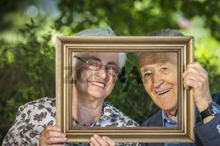 Retired couple looks through frame
