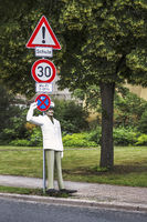 A policeman as a puppet points to many traffic signs