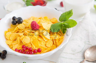 Fresh corn flakes with strawberries and milk close up Healthy tasty breakfast cornflakes with strawberries, raspberries, black currants and red currants